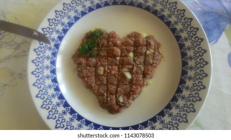 Raw kibe in heart shape served on the plate.
