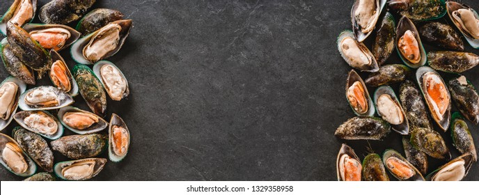 Raw kiwi mussels on slate stone background. Seafood, Shellfish, top view, flat lay, wide composition