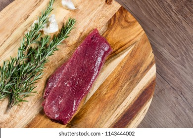 Raw lamb backstrap on chopping board with herbs