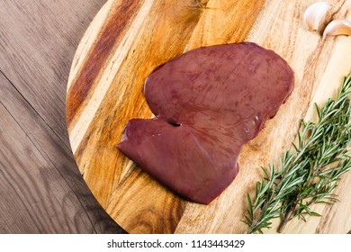 Raw lamb fry on chopping board with herbs