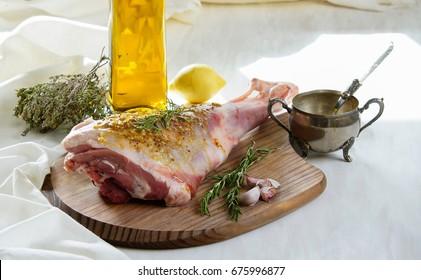 raw lamb leg with olive oil marinade