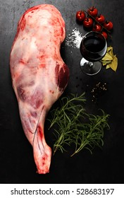 Raw lamb leg with spices for cooking on dark grange background