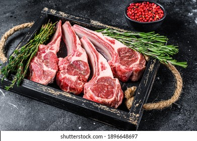 Raw lamb meat chops steaks in a wooden tray. Black background. Top view.