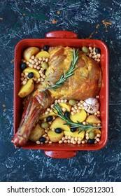 "Raw lamb's shoulder blade in roasting dish with potatoes, rosemary, chickpeas, garlic and ""ras el hanout"" seasoning. Selective focus."