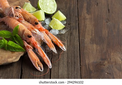 Raw langoustine on ice with lime and basil on wood