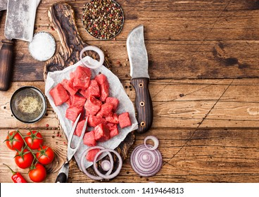 Raw lean diced casserole beef pork steak with vintage meat hatchet and knife on wooden background. Salt and pepper with fresh rosemary, red onion and garlic.