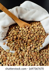 Raw lentils inside a white sack, wooden spoon on black wooden table