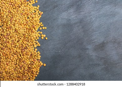 Raw lentils on balck stone background. Vegetarian food concept. Superfoods. Top view, copy space. Lentils are rich in complex carbohydrates, fiber, high in protein and make an excellent meat alternati