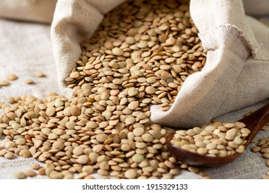 A lot of raw lentils poured out of a linen bag