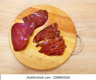 Raw liver on wooden board on wooden background.