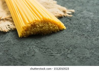 Raw long spaghetti on a black background. Yellow Italian pasta. Raw spaghetti bolognese. Spaghetti packaging concept.