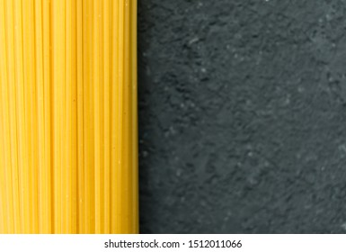 Raw long spaghetti on a black background. Yellow Italian pasta. Raw spaghetti bolognese. Copy space.