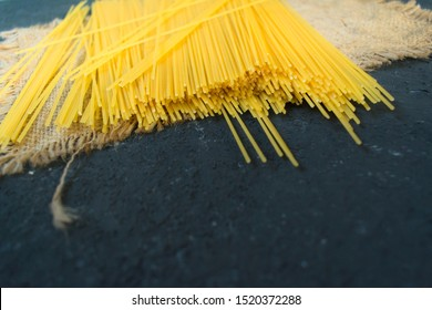 Raw long spaghetti on a black background. Yellow Italian pasta. Raw spaghetti bolognese. Spaghetti packaging concept.Copy space.