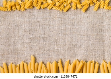 Raw macaroni with a blank placard for text. Various mix of pasta. Flat lay raw spilled Italian pasta. Diet and food concept.