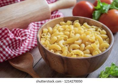 Raw macaroni pasta in wooden bowl