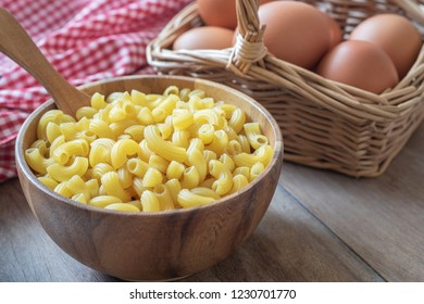 Raw macaroni pasta in wooden bowl and egg in basket