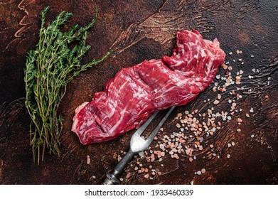 Raw machete skirt beef steak on meat fork. Dark background. Top view