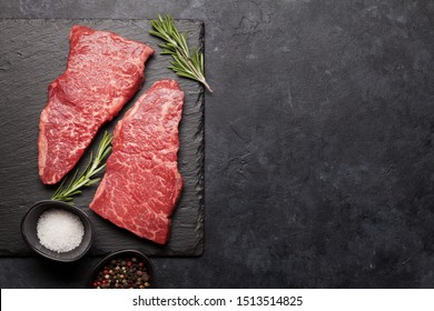 Raw marbled beef steak on stone board. Spices, utensils. Top view flat lay with copy space