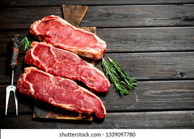Raw marbled beef steaks. On a wooden background.