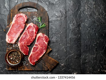 Raw marbled beef steaks with salt and spices. On a black rustic background.
