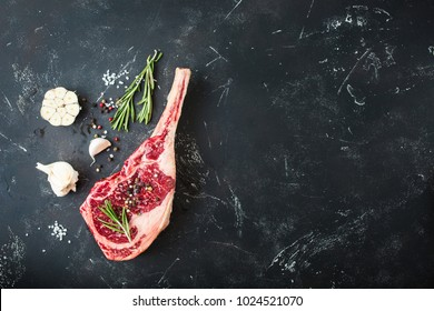 Raw marbled meat steak, herbs, seasonings, rustic stone background. Space for text. Beef Rib eye steak on bone, ready for cooking. Top view. Copy space. Ingredients for meat roasting. Tomahawk steak
