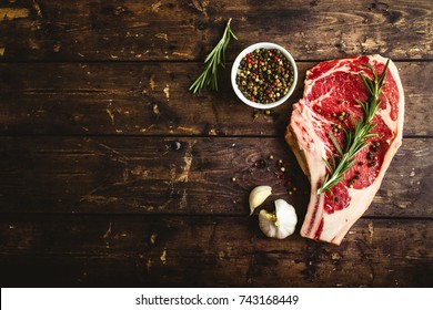 Raw marbled meat steak, pepper, herbs, garlic, old wooden background. Space for text. Beef Rib eye steak ready for cooking. Top view. Copy space. Ingredients, meat roasting. Ribeye meat steak. Closeup