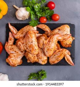 Rohe marinierte Hühnerflügel mit Gewürzen und Gemüse. Draufsicht, Kleiderschrank