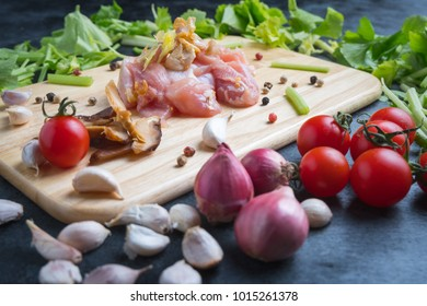 Raw materials for cooking Includes chicken, tomato, mushroom, onion, garlic and celery on black table.