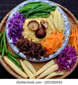 Raw materials for fry noodles mixed vegetables from top view, a Vietnamese vegetarian dish for vegans, with colorful greens, vermicelli and mushrooms, quick to  make for breakfast at home