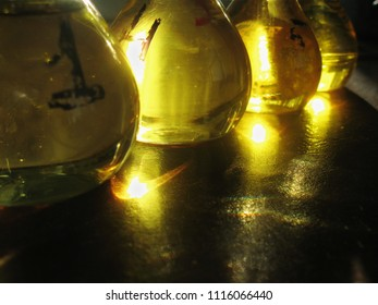 A raw of measuring flasks filled with yellow liquid. Old-stile chemical lab interior. The golden light shines in the flasks and reflects on a table surface. Still-life.