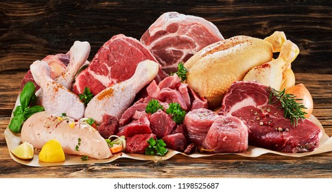Raw meat assortment, beef, chicken, turkey, decorated with greens and vegetables, placed on cooking paper on wooden table