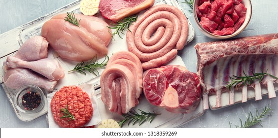 Raw meat - beef, pork, lamb, chicken with seasoning . Top view with copy space. Panorama, banner