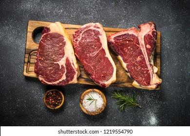 Raw meat beef steak. Black angus prime meat set - ribeye, striploin, t-bone steaks on cutting board. Top view on black table.