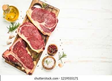Raw meat beef steak. Black angus prime meat set - ribeye, striploin, t-bone steaks on cutting board. Top view with copy space on white background.