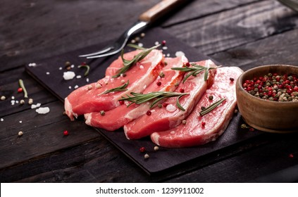 Raw meat. Raw beef steak on a cutting board with rosemary and spices on a black background.