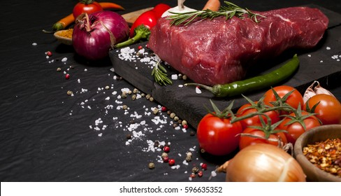 Raw meat. Raw beef steak on a cutting board with herbs and vegetables.
