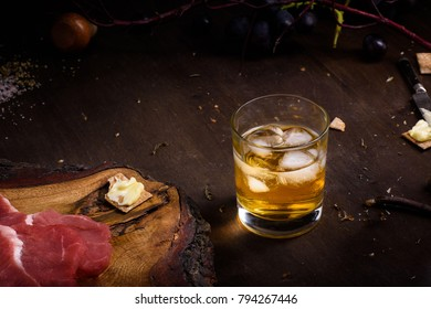 Raw meat, beef steak on wooden table, a glass of whiskey. Close up.