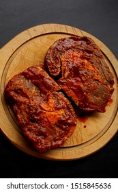 raw meat, beef steaks marinated in a red marinade, lie on a wooden round board, cooking concept, close-up