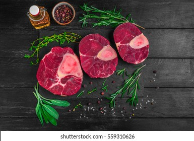 Raw meat beef veal shank slices meat for Osso Buco cooking on dark black wooden background. Ingredients for beef meat Osso Buco sage, thyme, rosemary, pepper, salt, pepper, vegetable oil. Top view