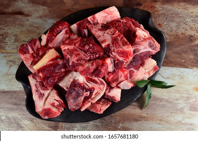Raw meat with bone on clay plate and brown stone background.Raw meat with beef bone. Beef bone selection for soup