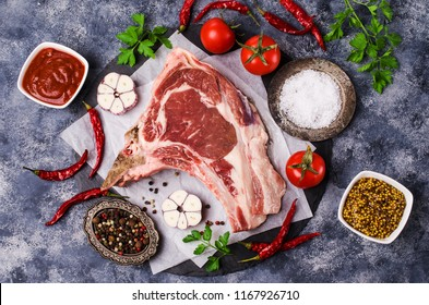 Raw meat with bones on a dark background with spices. Selective focus.