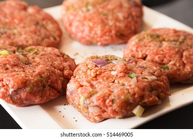 raw meat burger lies on a plate