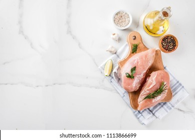 Raw meat, chicken breast filet, with olive oil, herbs and spices on white marble background, copy space top view