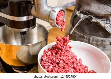 Raw meat coming out of the meat grinder as it is being minced.