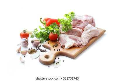 raw meat and different spices on wooden cutting board
