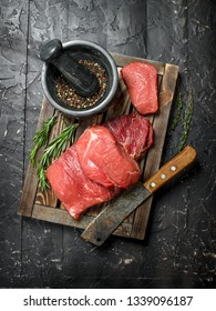 Raw meat. Fresh beef on a wooden tray with fragrant peppercorn and rosemary branches. On a black rustic background.