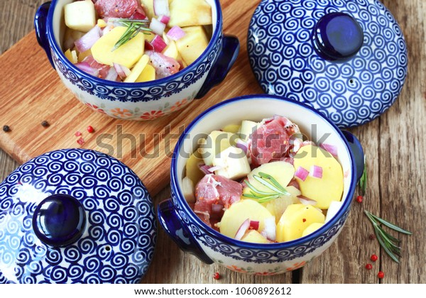 Raw meat (lamb) in ceramic pots with potatoes, eggplant, red onion and rosemary on a wooden table. Selective focus