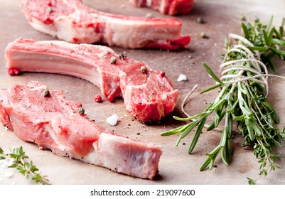 Raw meat, mutton, lamb rack with fresh herbs on a wooden background