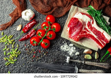 Raw meat on the kitchen table on a metallic background in a composition with cooking accessories