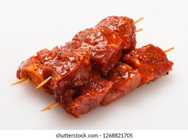 Raw meat on skewers in marinade with vegetables and spices.
